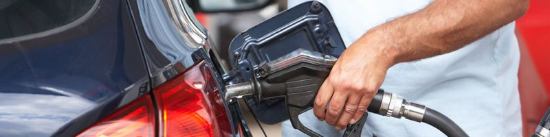Image of an adult filling car with gas at a service station